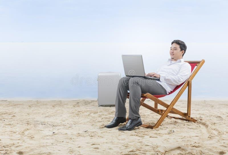 亚洲商人与膝上型计算机一起使用在海滩睡椅坐海滩 免版税库存图片