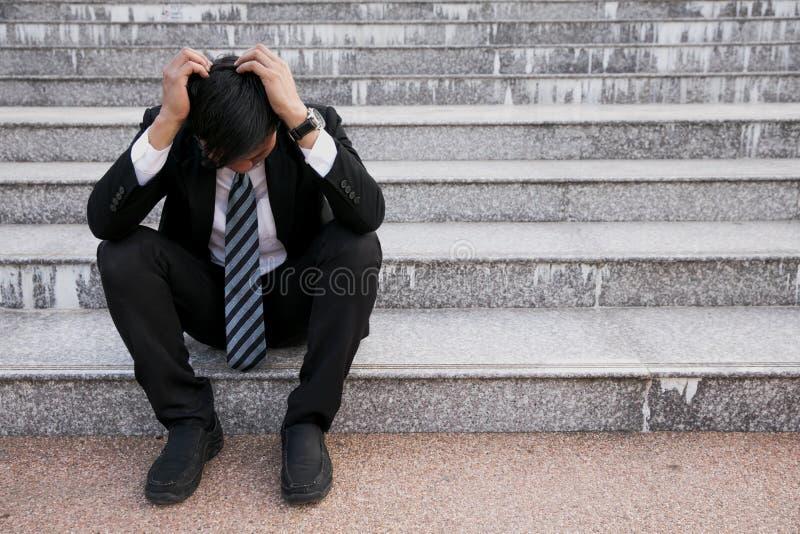 亚洲商人以头疼或偏头痛在市政厅在疲乏年轻商人的工作图象,重音,crisi以后 免版税库存照片