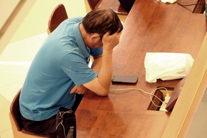 亚洲商人使用智能手机和注重从他的工作 消沉和忧虑概念 免版税库存图片