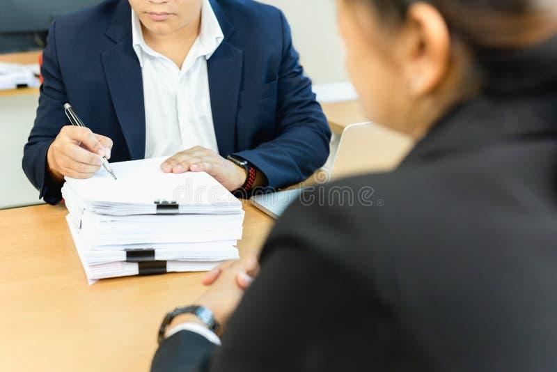 亚洲商人和他的辅助秘书签署的文件工作在办公室 免版税库存照片