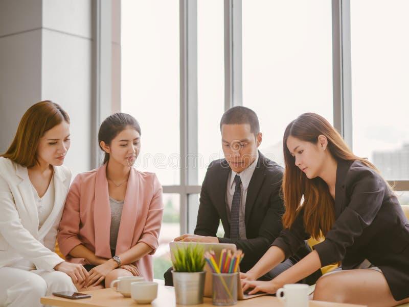 亚洲商人和女实业家谈论坐在会议桌上的工作在办公室 库存照片