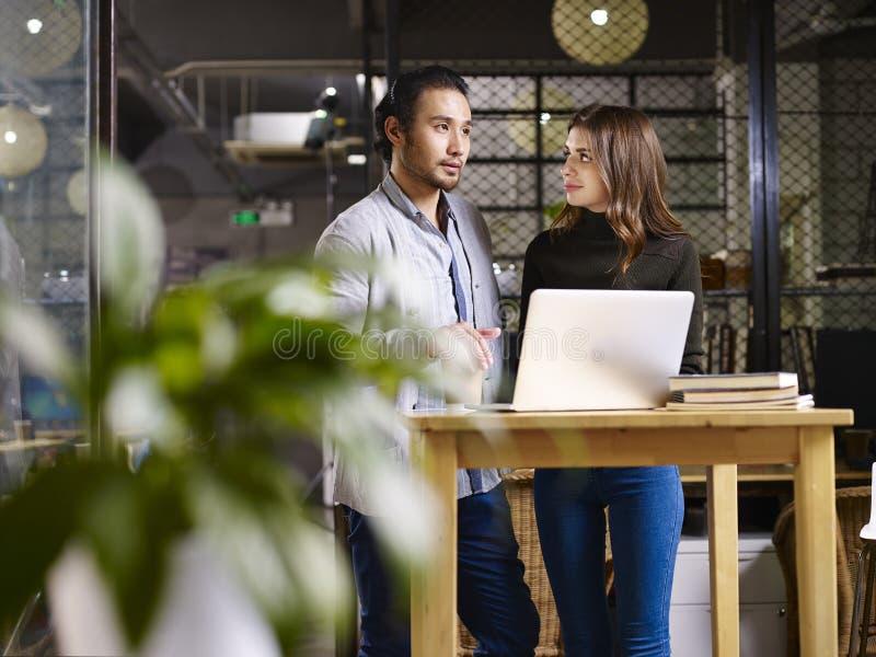 亚洲商人和白种人女实业家谈话在办公室 免版税库存图片
