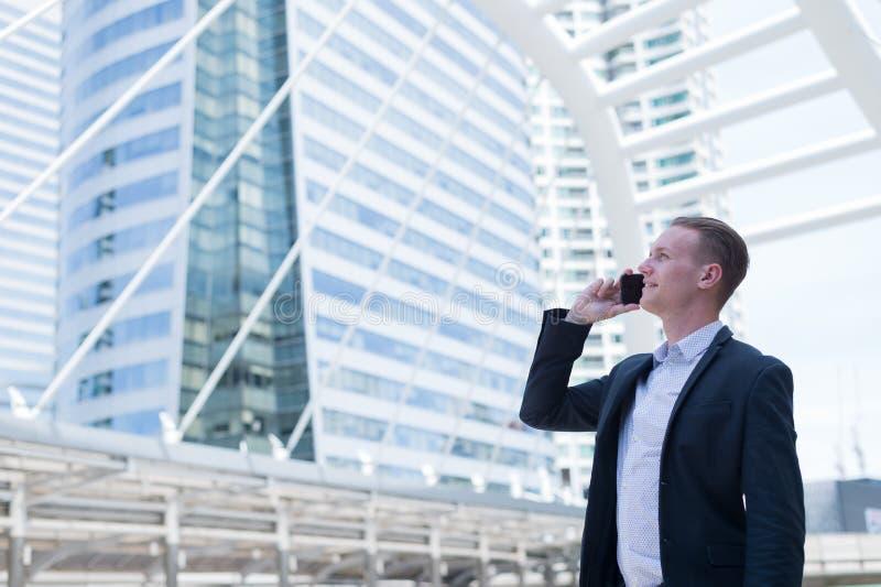 亚洲商人微笑和使用手机谈论企业成功和金融前景,与拷贝空间 免版税图库摄影