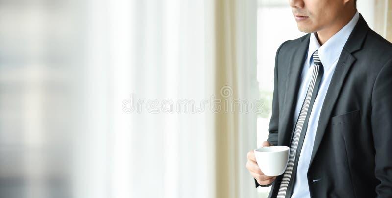 亚洲商人拿着一杯咖啡 免版税库存图片
