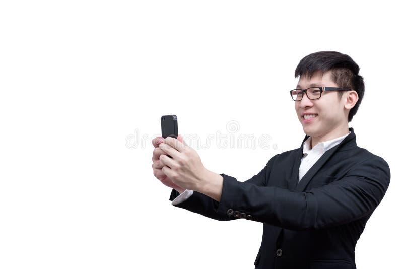 亚洲商人有拿着的一个电话与微笑一起使用和 免版税库存图片