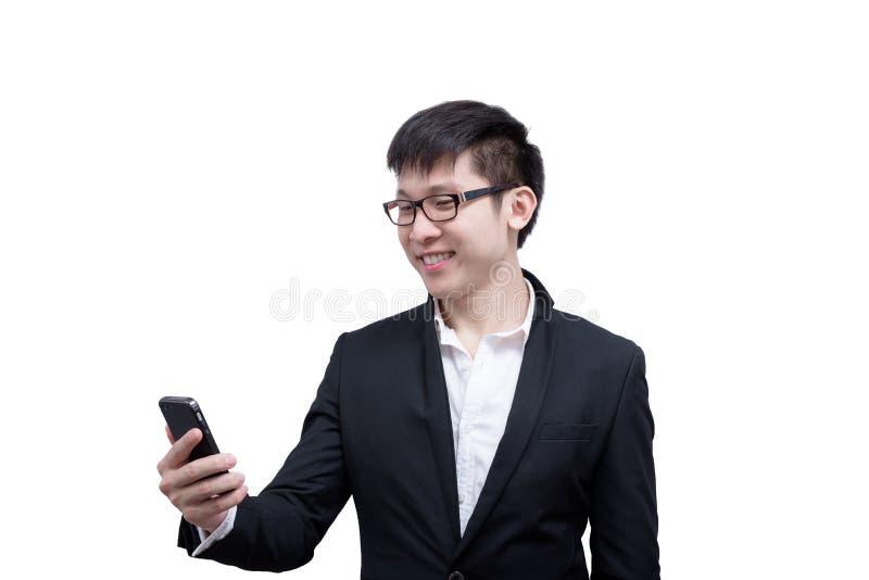 亚洲商人有拿着的一个电话与微笑一起使用和 免版税库存照片