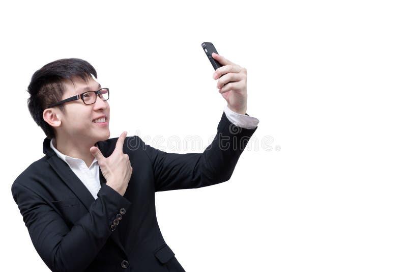 亚洲商人有拿着selfie的一个电话与微笑和h 库存照片