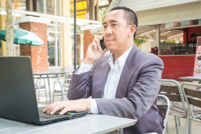 亚洲商人用途无线数字式智能手机和膝上型计算机或者 免版税库存图片