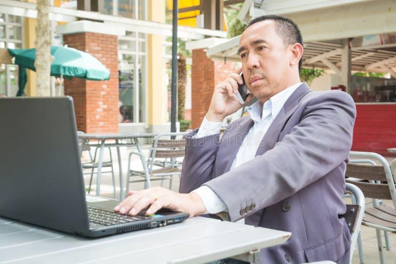 亚洲商人用途无线数字式智能手机和膝上型计算机或者 免版税图库摄影