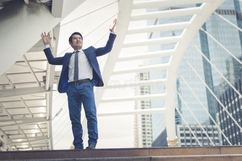 亚洲商人立场和举庆祝两只的手对快乐和他的成功在事业和使命 免版税库存照片