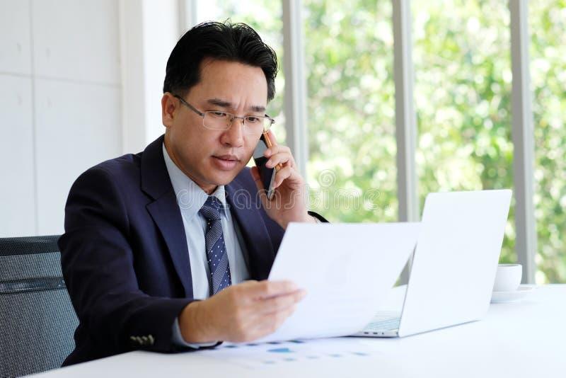 亚洲商人读书报纸谈电话和与手提电脑一起使用在办公室,企业概念 库存图片
