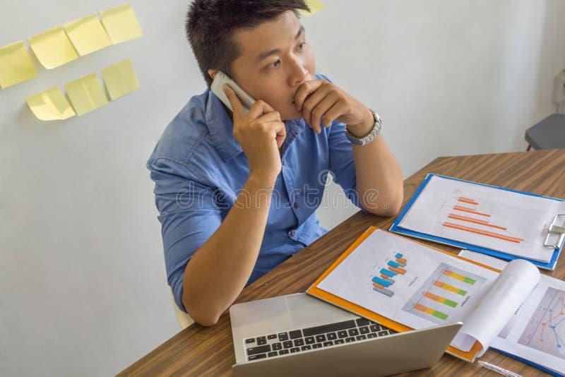 亚洲商人谈话在关于事务的智能手机 库存图片