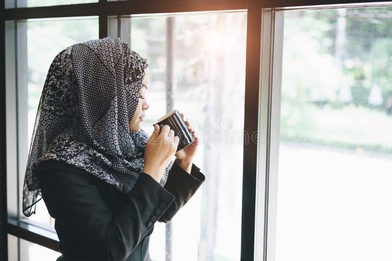 亚洲回教女商人气味和饮用的咖啡 免版税库存照片