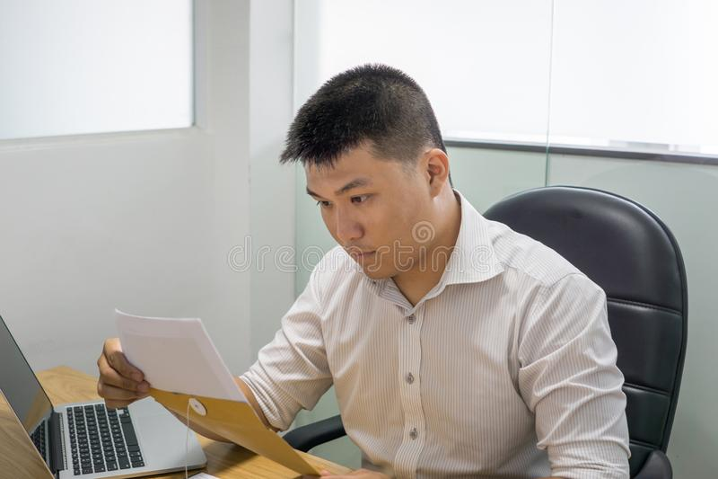 亚洲在文件的商人读的财政数字 图库摄影