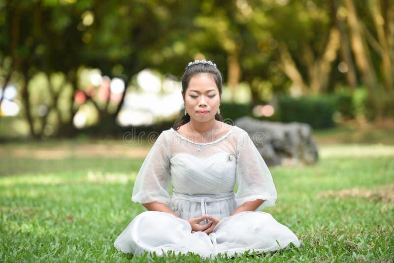 亚洲在绿草的妇女凝思 免版税库存图片
