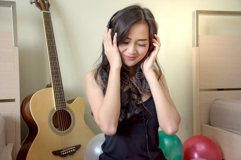 亚洲在耳机的妇女感受愉快的听的音乐有五颜六色的气球的 免版税库存图片