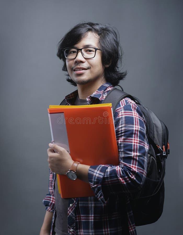 亚洲大学生微笑画象在照相机的,当举行时 库存照片