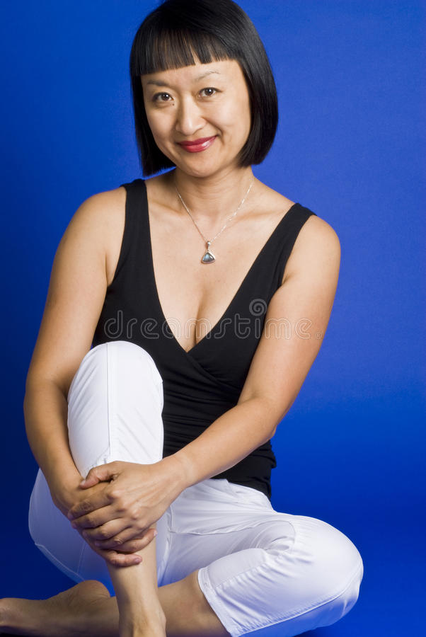 亚洲头发短的坐的微笑的妇女 免版税库存照片