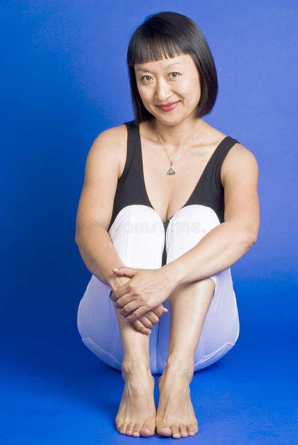 亚洲头发短的坐的微笑的妇女 免版税库存图片