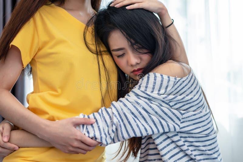 亚洲女友安慰秀丽哀伤的女孩 人们和社会问题问题概念 生活方式和友谊题材 免版税图库摄影