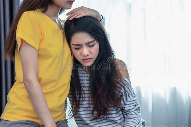 亚洲女友安慰秀丽哀伤的女孩 人们和社会问题问题概念 生活方式和友谊题材 免版税库存照片