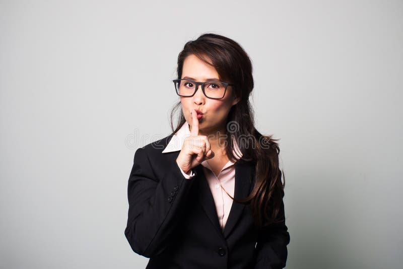 亚洲女商人用途手指嘘 沉寂的标志 图库摄影