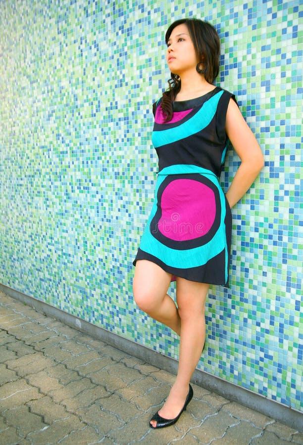 亚洲女孩倾斜偏僻的俏丽的认为的墙&# 免版税图库摄影