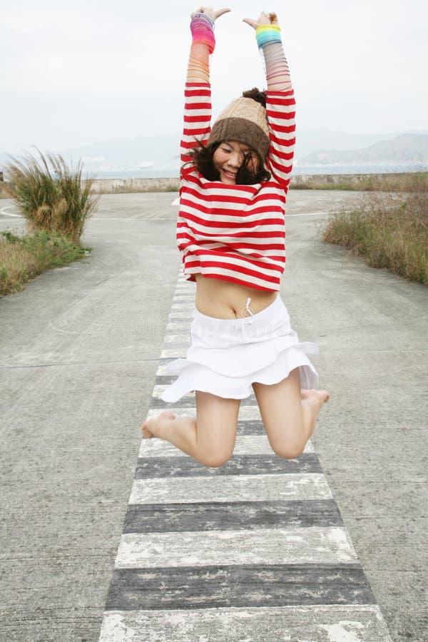 亚洲女孩喜悦跳 免版税库存图片