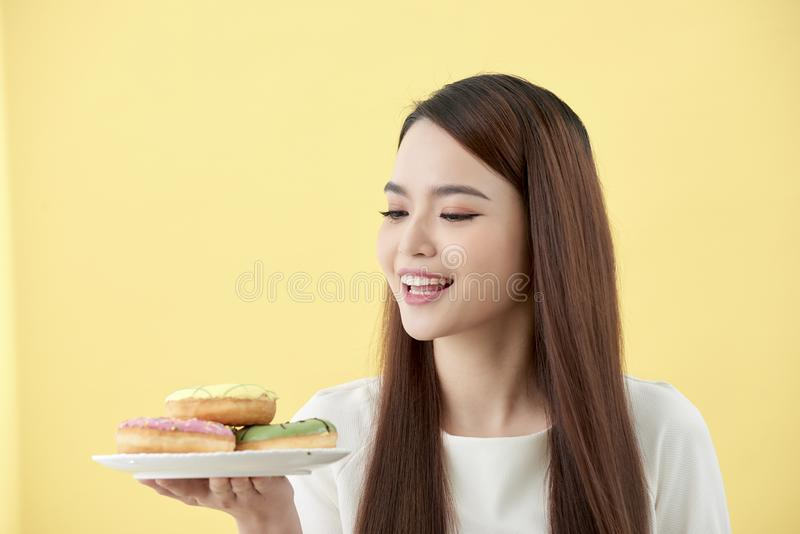 亚洲女孩展示和举行板材在微笑的鲜美可口芳香油炸圈饼充分面对隔绝 库存图片