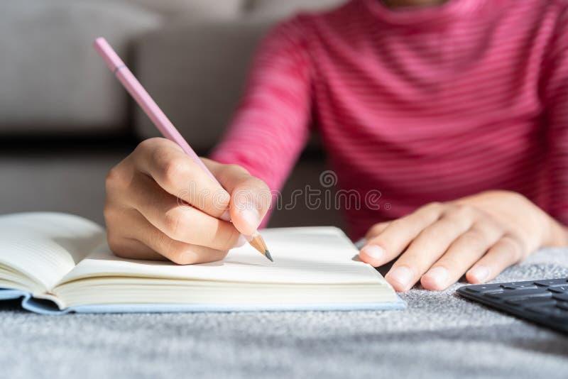 亚洲女孩的手正通过互联网写笔记和做家庭作业,在家和家中的起居室里学习 免版税库存照片