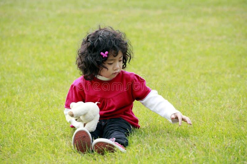 亚洲女孩草使用的一点 免版税库存图片