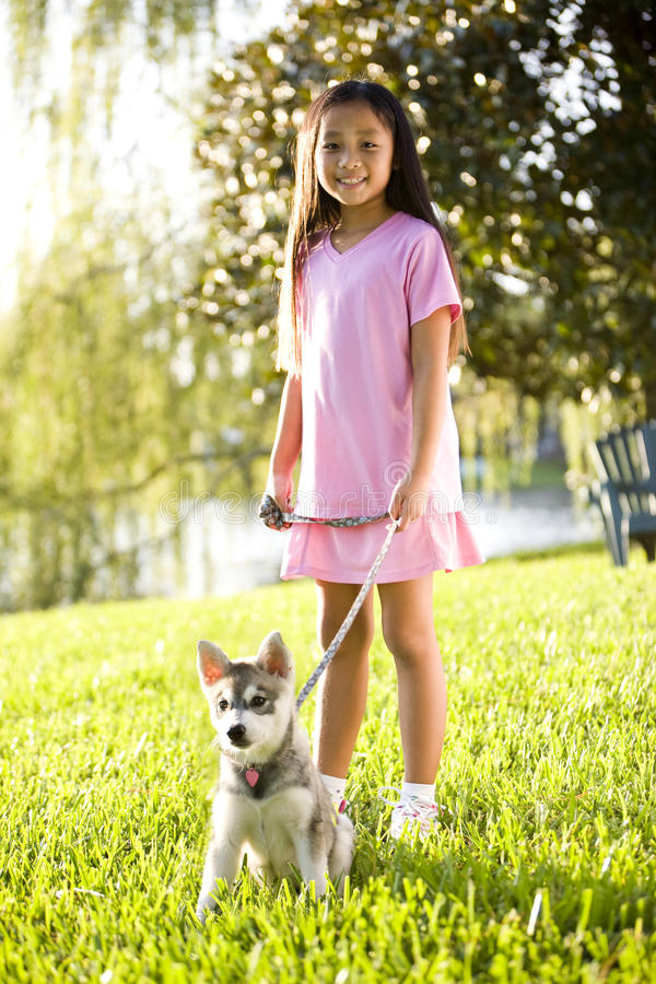 亚洲女孩草皮带小狗走的年轻人 库存图片