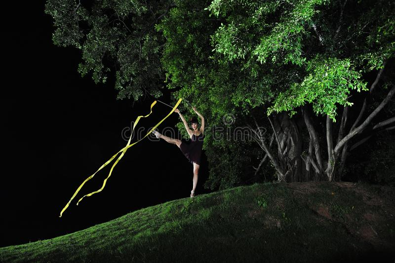 亚洲女孩跳舞芭蕾在大树下在晚上 免版税库存照片