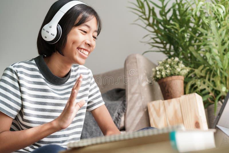 亚洲女孩通过平板电脑网络导师在网上挥手致意,亚洲孩子正在学习,向早安老师问好 免版税库存图片