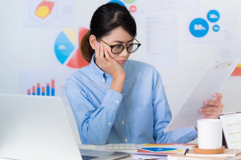亚洲女实业家薪水注意,当工作事务和fi时 免版税图库摄影