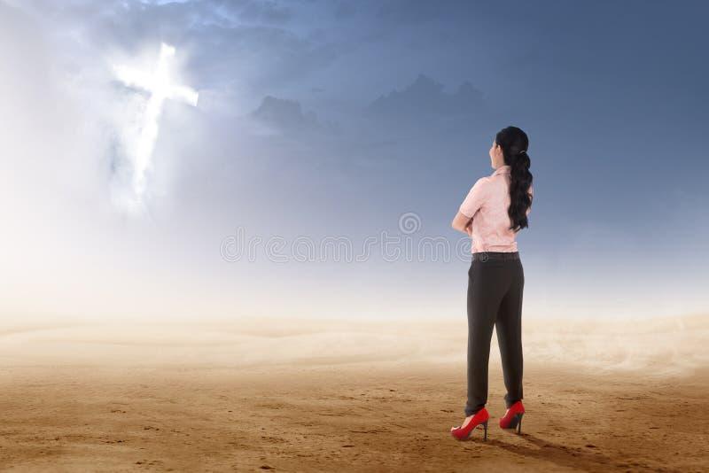 亚洲女实业家身分和看发光的基督徒十字架背面图在沙漠的 库存图片