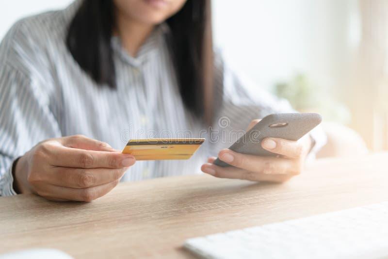 亚洲女性的特写手正在网上购买信用卡 女人在智能手机上输入号码银行,在网上做电话 免版税库存照片