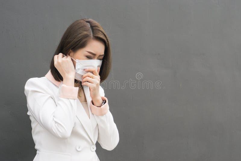 亚洲女服防护面罩在有咳嗽的污染城市 库存照片
