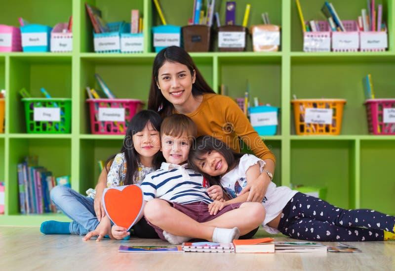 亚洲女老师教的拥抱混合的族种小组孩子在教室,幼儿园前学校概念 图库摄影