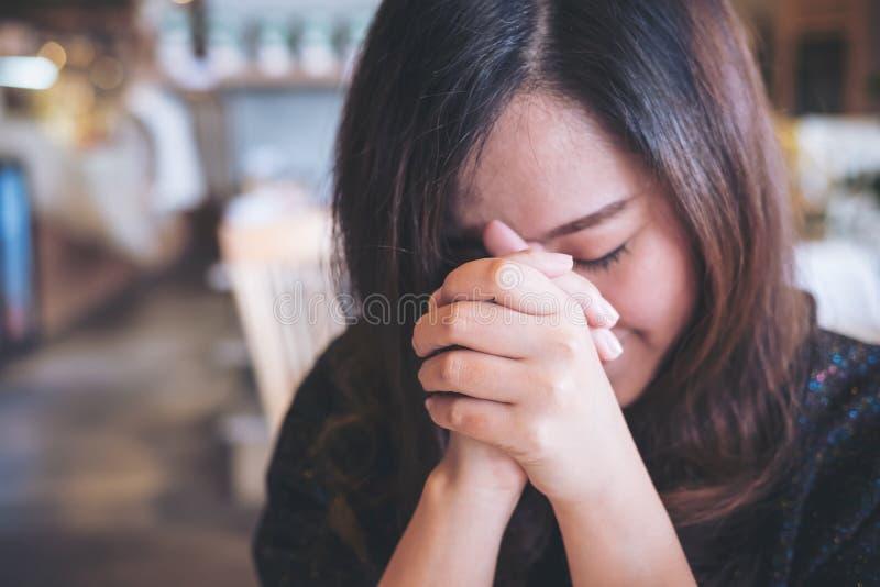 亚洲妇女关闭她的对祈祷和祝愿的眼睛好运 免版税库存照片