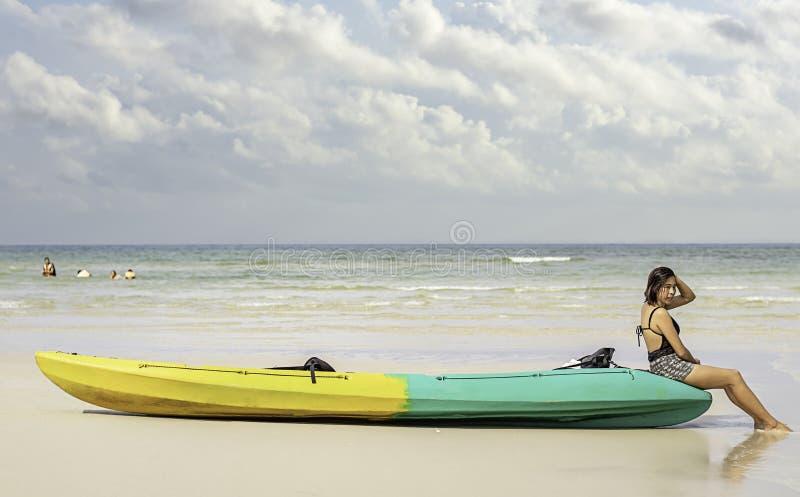 亚洲妇女和皮船在海滩背景海和天空在酸值Kood,桐艾府在泰国 免版税图库摄影
