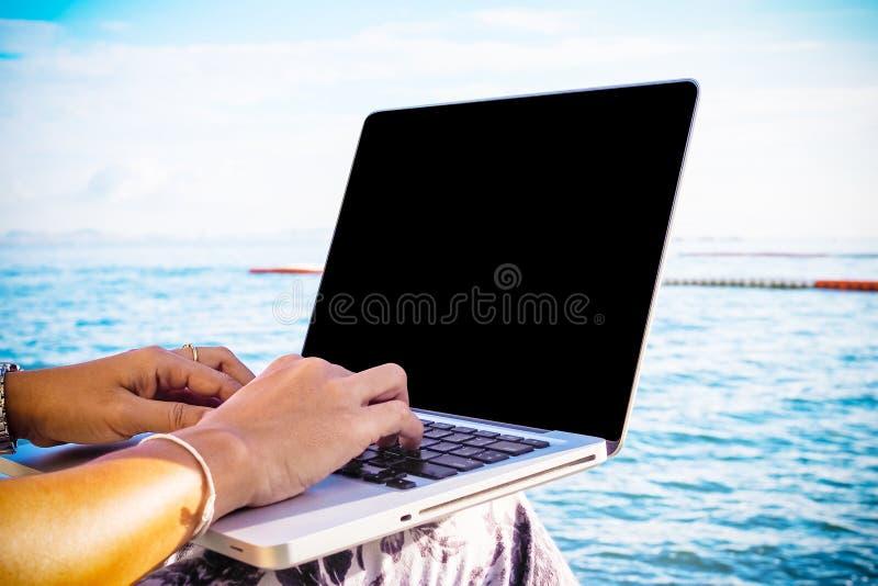 亚洲妇女商人与手提电脑一起使用在海旁边在夏天 库存图片