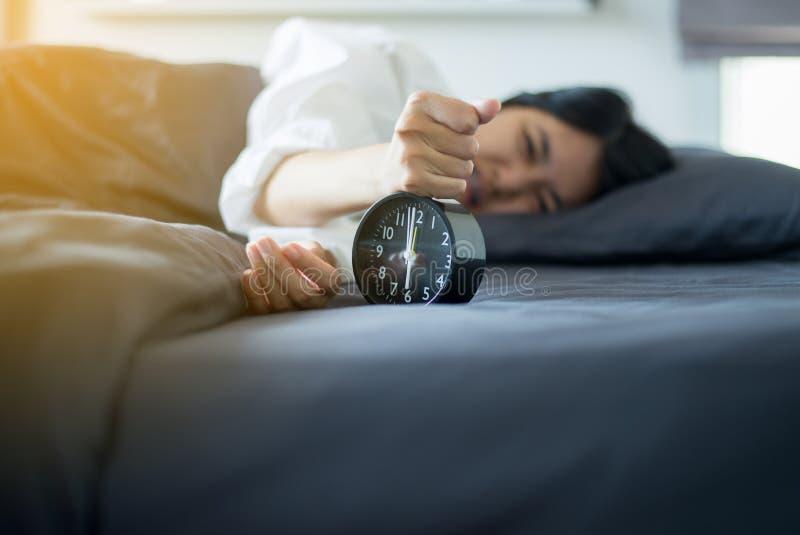 亚洲妇女怨恨得到强调了叫醒早早晨6点,闹钟 库存照片