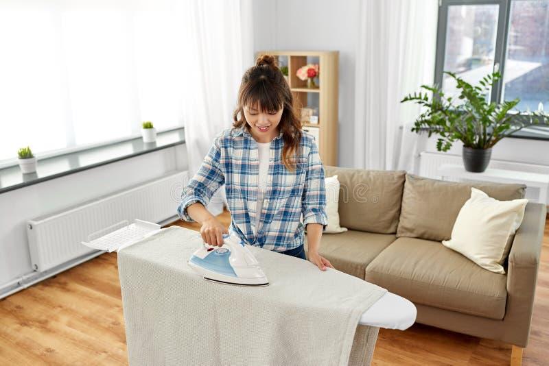 亚洲妇女或主妇电烙的床单在家 免版税库存照片