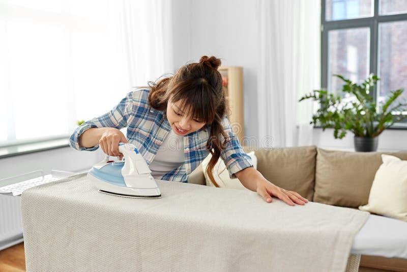 亚洲妇女或主妇电烙的床单在家 库存图片