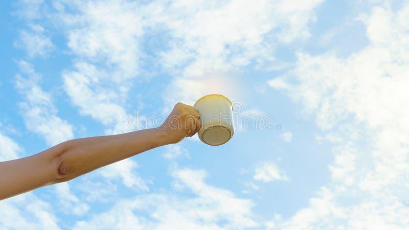 亚洲妇女手拿着热的咖啡杯室外在与拷贝空间的清楚的天空背景 Enjoy饮用的咖啡早晨 免版税库存照片