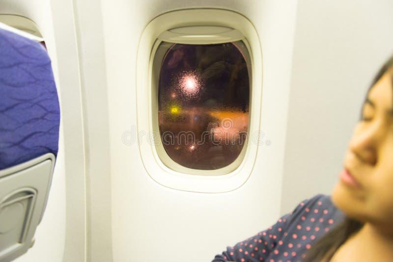 亚洲妇女旅行家睡觉选址在飞机的窗口附近在飞行期间 免版税库存图片