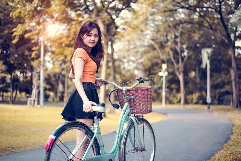 亚洲妇女画象在有自行车的公园 人和生活方式概念 放松和活动题材 免版税库存照片