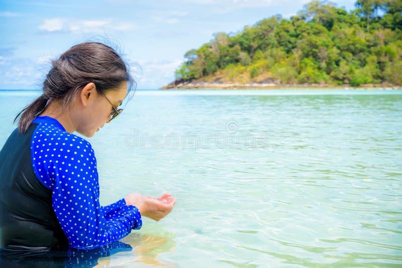 亚洲妇女看看清楚的水在他们的手上在海 库存照片