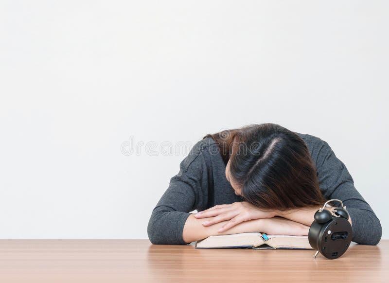 亚洲妇女睡眠在书桌上说谎,在她从在被弄脏的棕色木书桌上后的阅读书疲倦了,并且白水泥墙壁构造了ba 图库摄影